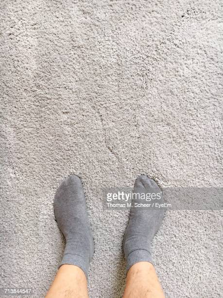 low section of man standing on carpet - tapijt stockfoto's en -beelden