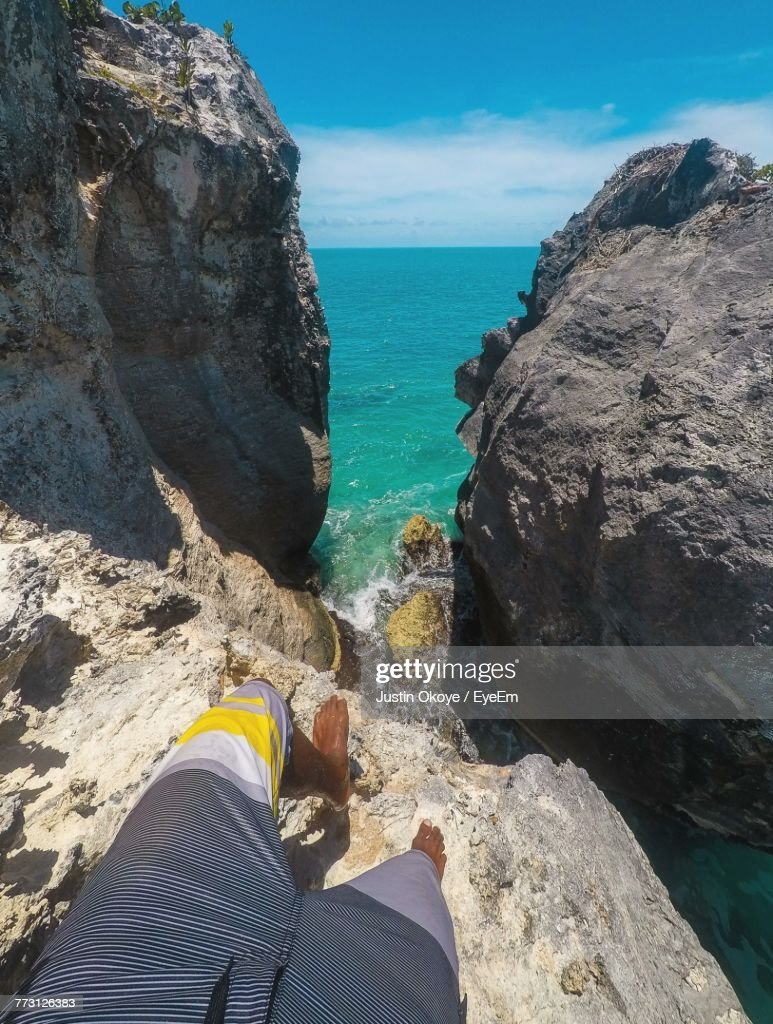 Low Section Of Man Standing On Cliff By Sea Against Sky : Photo