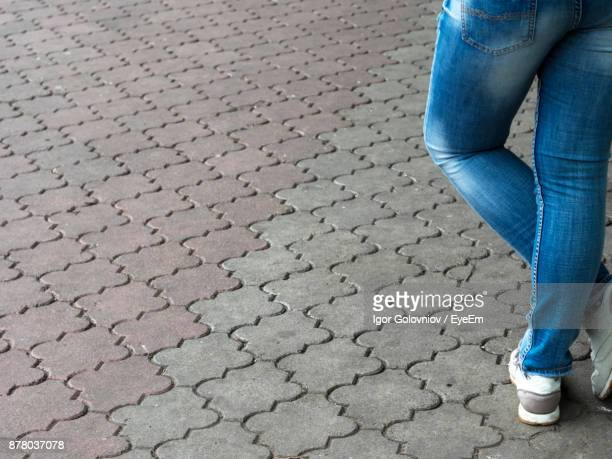 low section of man standing on cobble street - igor golovniov stock pictures, royalty-free photos & images