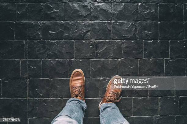 Low Section Of Man Standing On Cobblestone