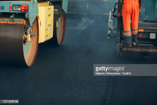 low section of man standing on construction vehicle - low section stock pictures, royalty-free photos & images