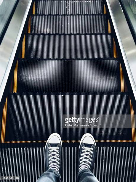low section of man standing on escalator - escalator stock pictures, royalty-free photos & images