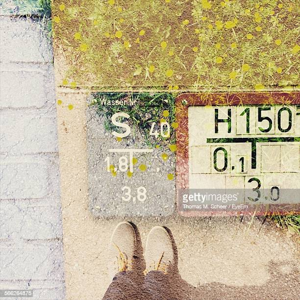 Low Section Of Man Standing On Field And Sign
