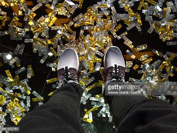Low Section Of Man Standing On Floor Covered With Confetti