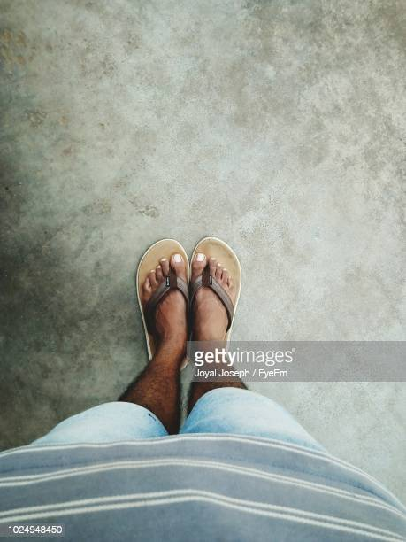 low section of man standing on floor - open toe stock pictures, royalty-free photos & images