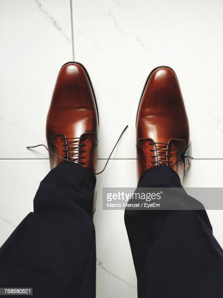 low section of man standing on floor - chaussures en cuir photos et images de collection
