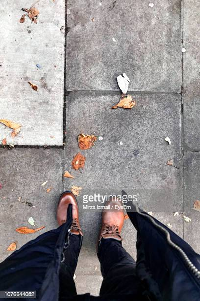 low section of man standing on footpath - pavement stock pictures, royalty-free photos & images