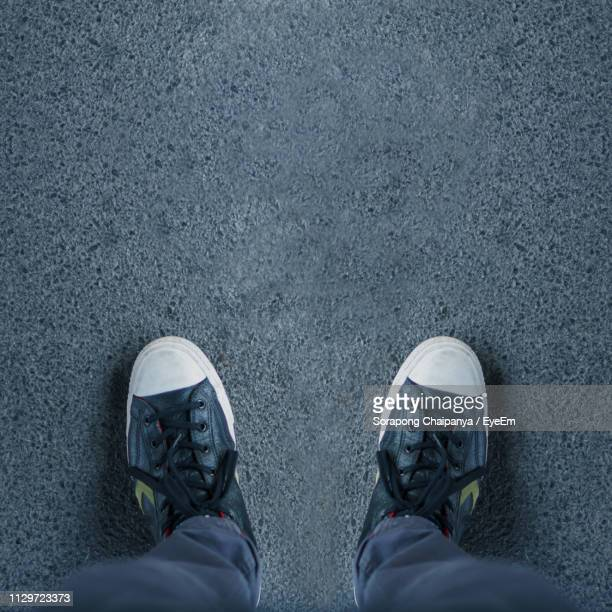 low section of man standing on footpath - human foot stock pictures, royalty-free photos & images