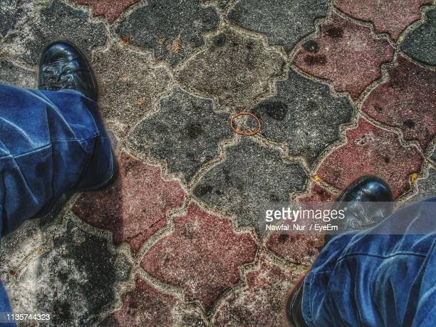 low section of man standing on footpath - nawfal nur stock pictures, royalty-free photos & images