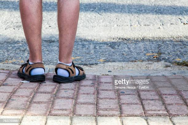 low section of man standing on footpath - open toe stock pictures, royalty-free photos & images