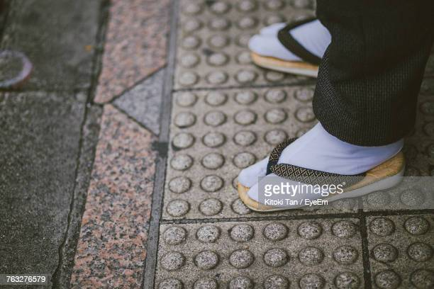 Low Section Of Man Standing On Footpath
