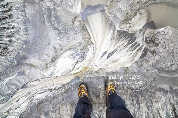 Low Section Of Man Standing On Glacier