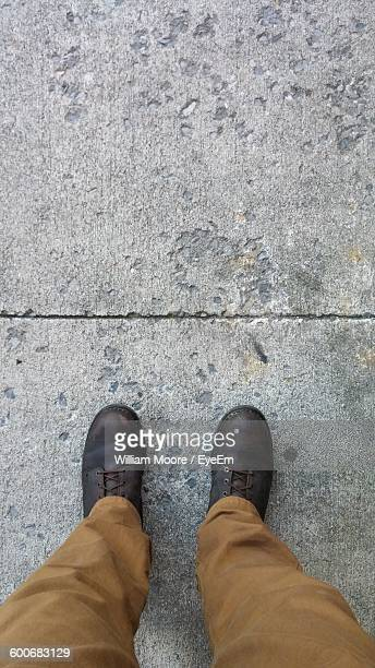 Low Section Of Man Standing On Ground