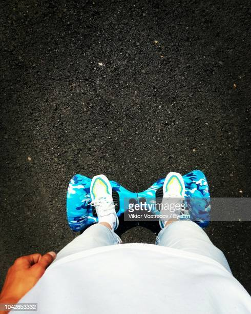 low section of man standing on hoverboard at road - hoverboard stock pictures, royalty-free photos & images