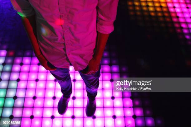 low section of man standing on illuminated dance floor - purple shoe stock pictures, royalty-free photos & images