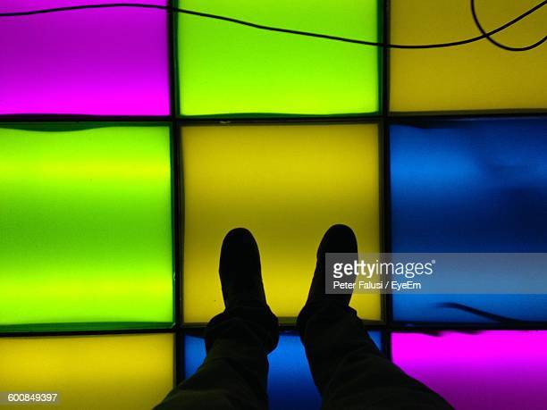 Low Section Of Man Standing On Illuminated Floor At Nightclub