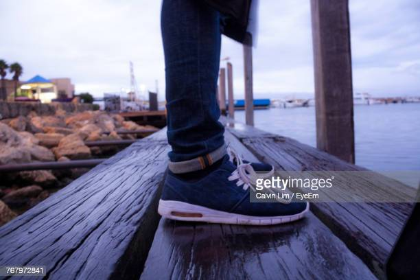 Low Section Of Man Standing On Jetty