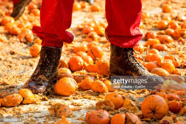 Low Section Of Man Standing On Messy Smashed Oranges