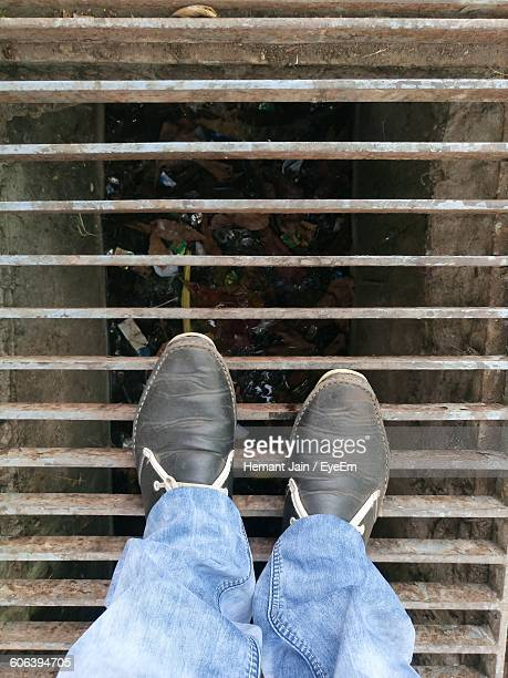 Low Section Of Man Standing On Metal Grate Over Sewage