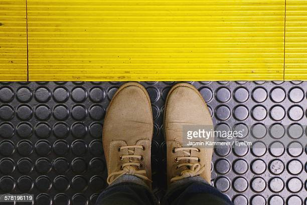 low section of man standing on metallic floor - yellow shoe stock pictures, royalty-free photos & images