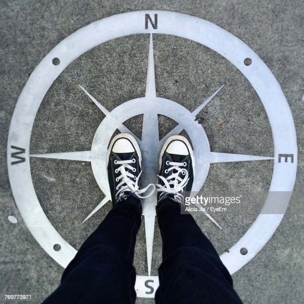 low section of man standing on navigation sign - compass stock pictures, royalty-free photos & images