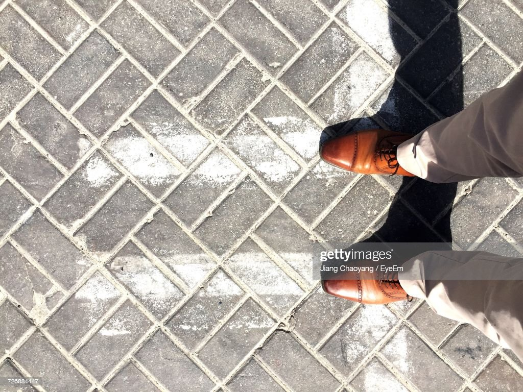 Low Section Of Man Standing On Paved Floor : Stock Photo