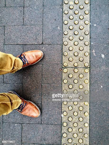 low section of man standing on paved street - brown shoe stock photos and pictures