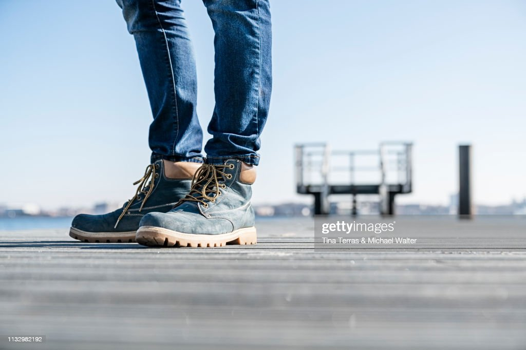 Low section of man standing on pier on sunny day in Germany. : Stock Photo