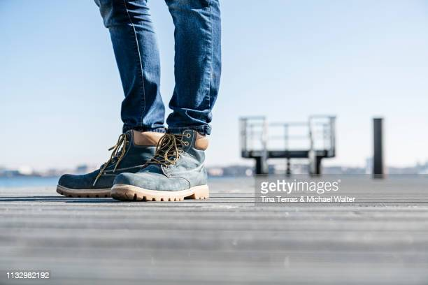 low section of man standing on pier on sunny day in germany. - sonnig imagens e fotografias de stock