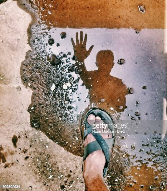 low section of man standing on puddle - nazar stock photos and pictures