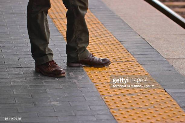 low section of man standing on railroad station platform - antonella di martino foto e immagini stock
