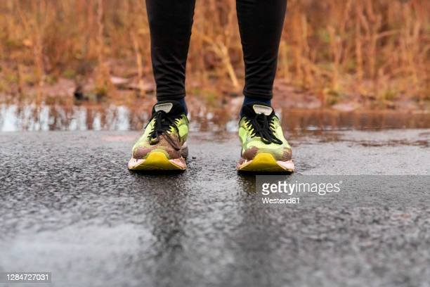 low section of man standing on road during rainy season - back stock pictures, royalty-free photos & images