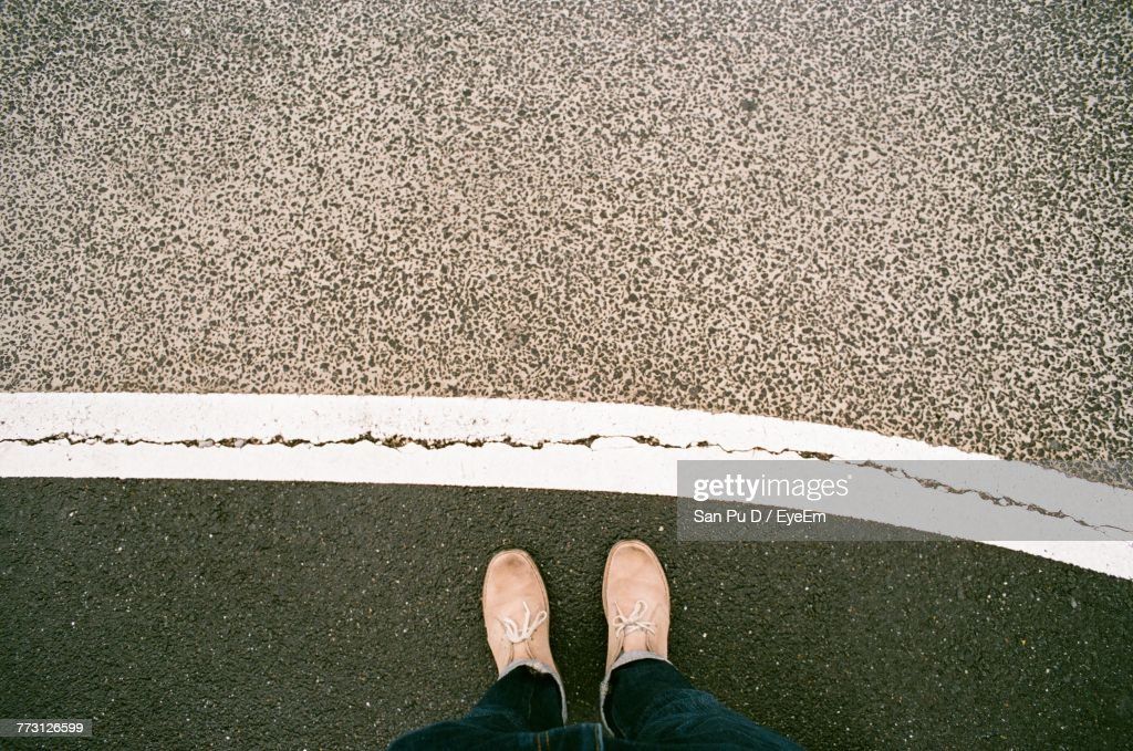 Low Section Of Man Standing On Road : Photo