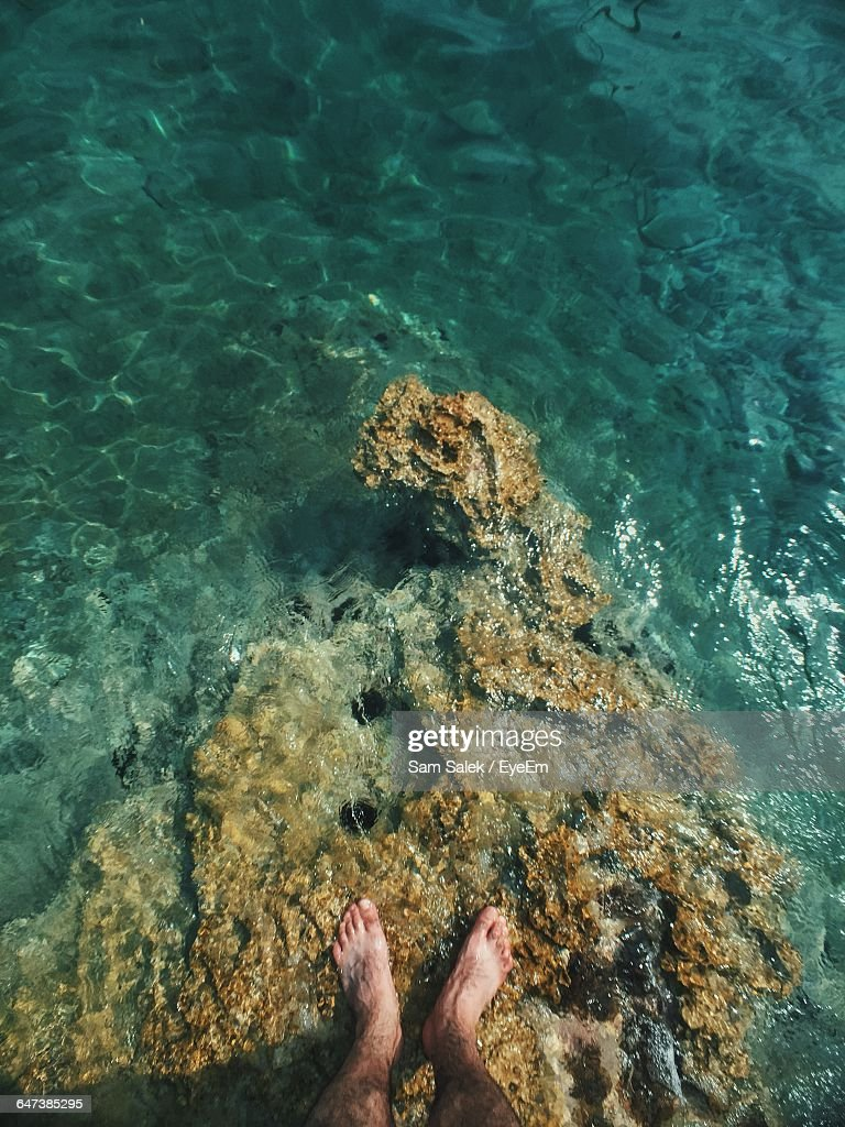 Low Section Of Man Standing On Rock In Sea : Stock Photo