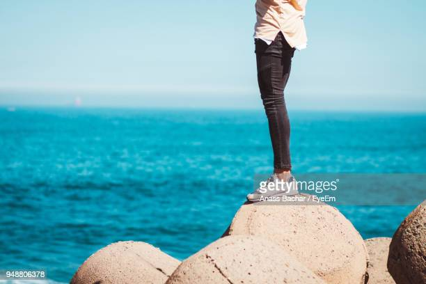Low Section Of Man Standing On Rock Over Sea