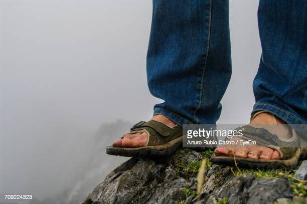 Low Section Of Man Standing On Rock