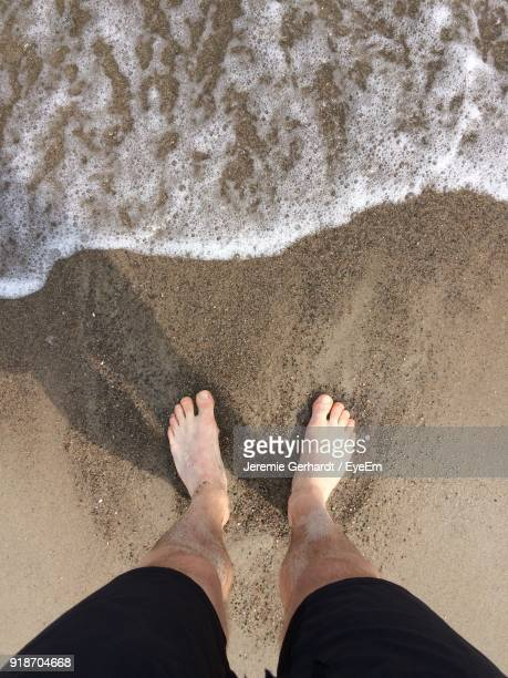 Low Section Of Man Standing On Sand At Beach