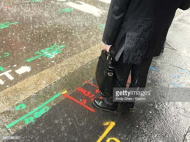 low section of man standing on sidewalk with road markings in rain - sydney rain stock pictures, royalty-free photos & images