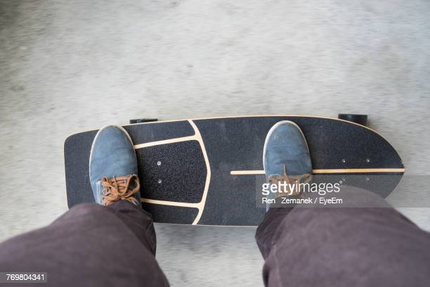 Low Section Of Man Standing On Skateboard