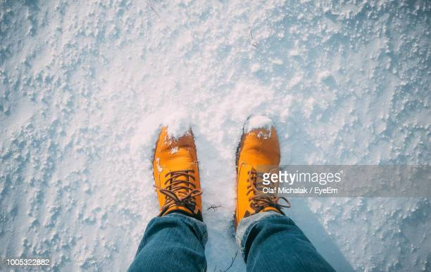 low section of man standing on snow covered field - human foot stock pictures, royalty-free photos & images