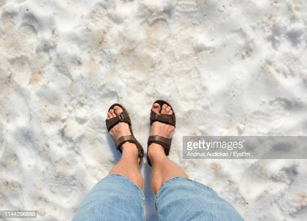 low section of man standing on snow - open toe stock pictures, royalty-free photos & images