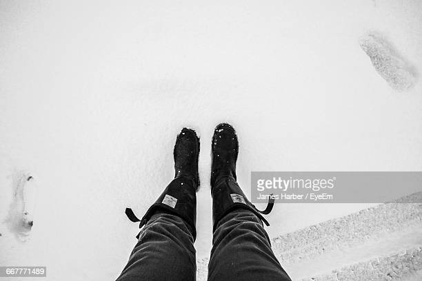Low Section Of Man Standing On Snow