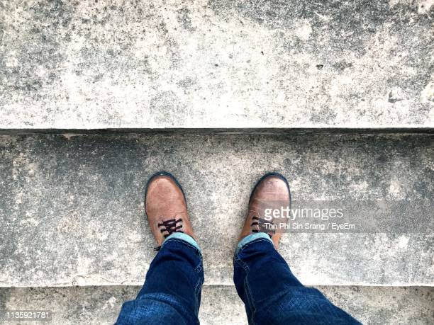 low section of man standing on steps - sezione inferiore foto e immagini stock
