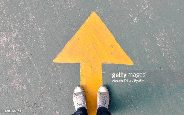 low section of man standing on street by arrow symbol - direction stock pictures, royalty-free photos & images