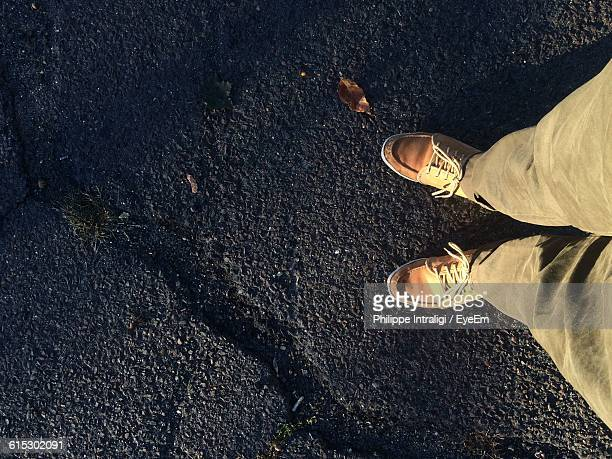 Low Section Of Man Standing On Street