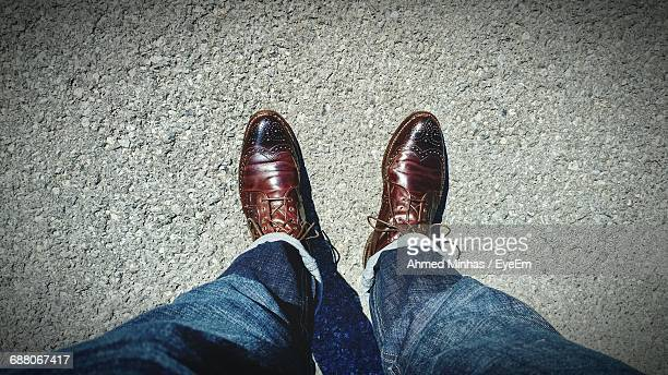 low section of man standing on street - brown shoe stock pictures, royalty-free photos & images