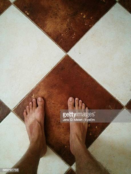 Low Section Of Man Standing On Tiled Floor At Home