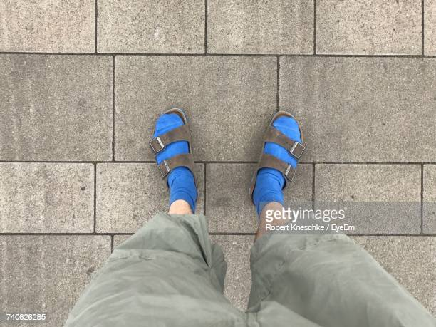 low section of man standing on walkway - sandal stock pictures, royalty-free photos & images