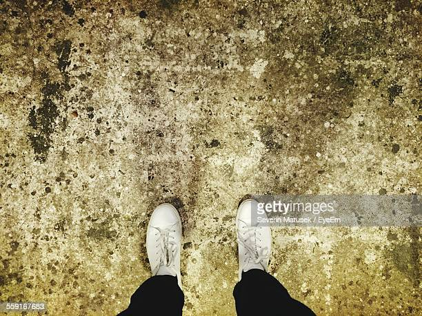Low Section Of Man Standing On Weathered Floor