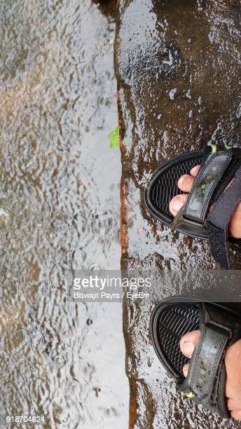 Low Section Of Man Standing On Wet Road